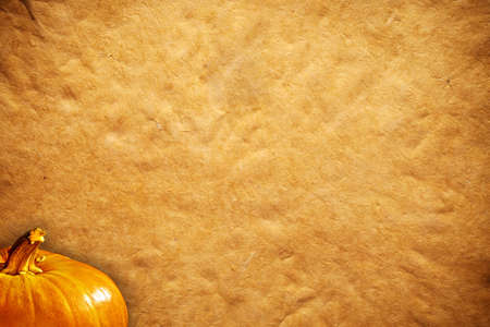 orange pumpkins and sheet of paper background photo