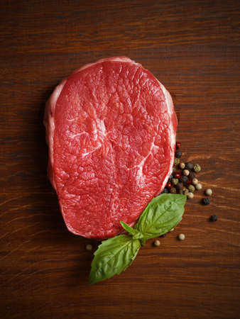 fresh raw steak with pepper and basil on the wooden board.  photo