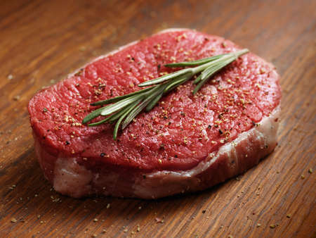 fresh raw steak with pepper and rosemary on the wooden board.  photo