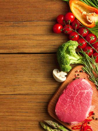 comidas saludables: Filete crudo con espárragos verdes y verduras sobre plancha de madera