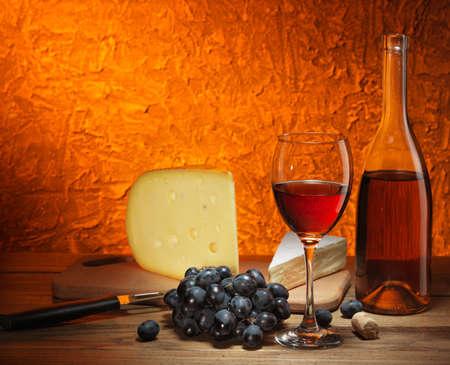 pan y vino: Bodegón con queso, uvas y vidrio y una botella de vino tinto. Foto de archivo