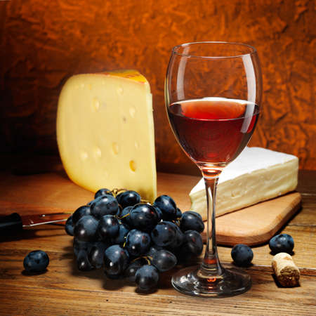 Still-life with cheese, grapes and glass of red wine. photo