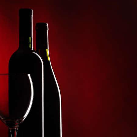 Bottiglia e bicchiere di vino rosso su sfondo rosso scuro