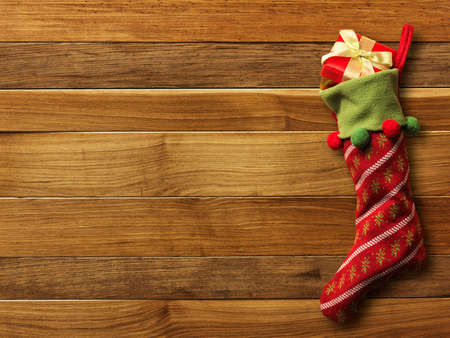 Christmas sock with presents on wood board photo