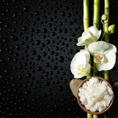 spa candle: bowl of salt and orchid, bamboo on black Stock Photo