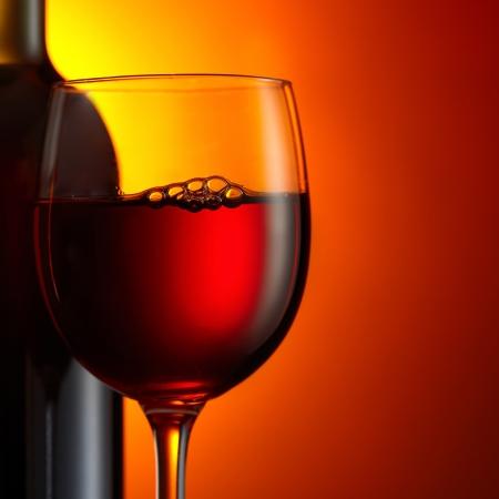 ボトルと濃い赤の背景に赤ワインのガラス