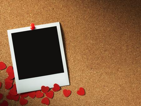 Marcos de fotos estilo polaroid sobre panel de corcho con corazón de papel Foto de archivo - 25647371