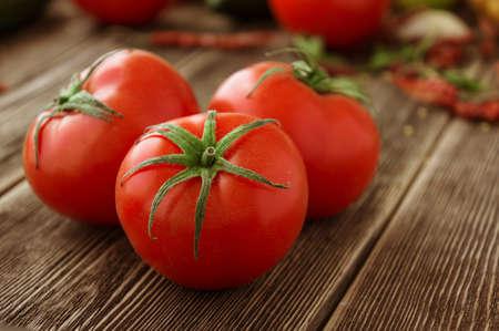 Close-up of fresh, ripe tomatoes on wood background Stock Photo