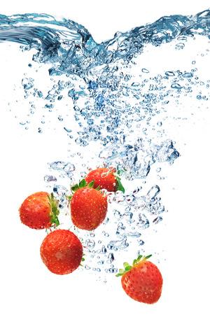 新鮮なイチゴを白で隔離スプラッシュ水に落とした 写真素材