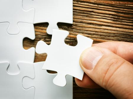 ジグソー パズルのピースを不足している手。最終パズル piece.wooden 背景を完了するためのビジネス コンセプト イメージ 写真素材