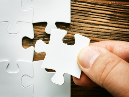 Hand with missing jigsaw puzzle piece. Business concept image for completing the final puzzle piece.wooden background Banque d'images