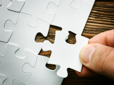Hand with missing jigsaw puzzle piece. Business concept image for completing the final puzzle piece.wooden background Фото со стока