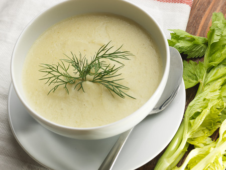 Top view of a bowl of celery soup on a rustic background. Close up