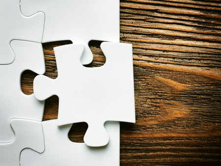 Hand with missing jigsaw puzzle piece. Business concept image for completing the final puzzle piece.wooden background Stockfoto