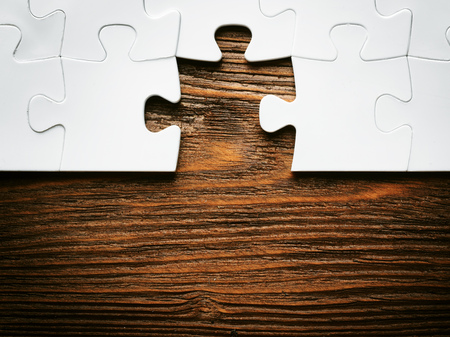 Placing missing a piece of puzzle. business concept. wooden background Stockfoto