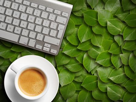 coffee mug and keyboard. background of green leaves