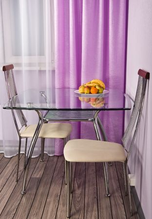 Kitchen corner with a glass table and fruit photo