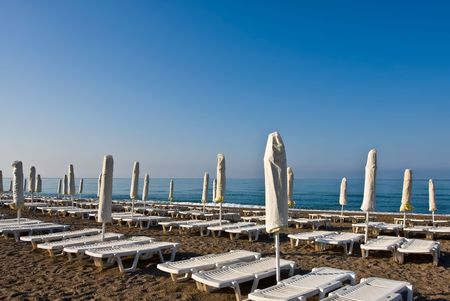 accurately: A number of plank beds and umbrellas on a beach along the sea