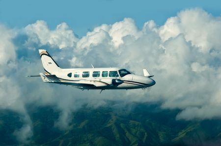 clearness: The flying plane against clouds and green hills