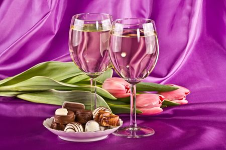 Two glasses of white wine, flowers and sweets on a lilac background photo