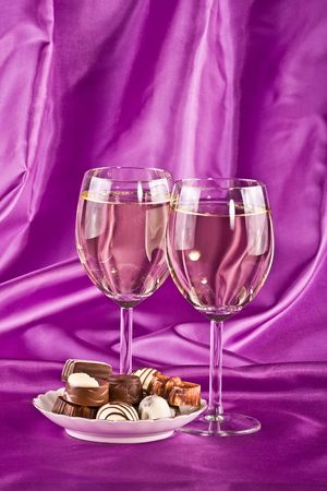 Two glasses of white wine and sweet on a lilac background photo