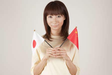 bandera japon: Mujer joven sosteniendo la Bandera japonesa y bandera China