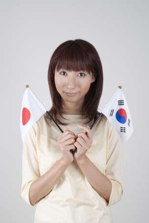 bandera japon: Joven, sosteniendo la Bandera japonesa y coreana de la bandera