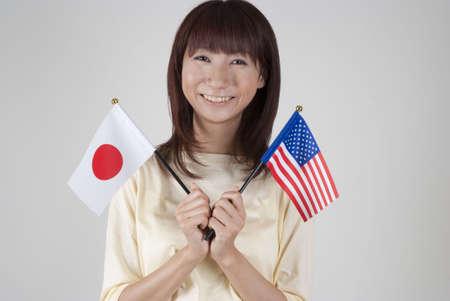 bandera japon: Mujer joven sosteniendo la Bandera japonesa y la bandera de Estados Unidos