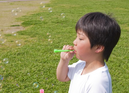 nine years old: Boy blowing bubbles Stock Photo