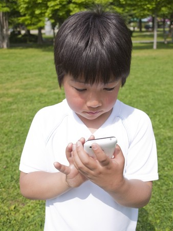 nine years old: Boy using cellular phone