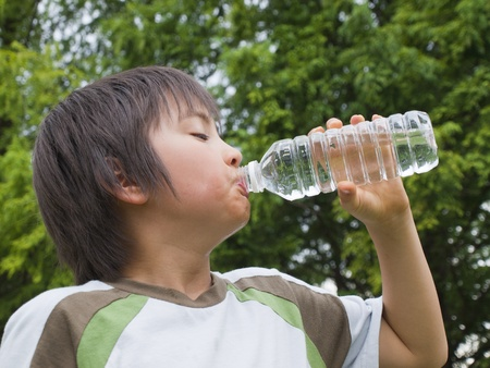 standing water: Boy drinking mineral water Stock Photo