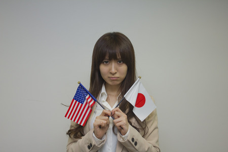american flags: Business woman holding American and Japanese flags Stock Photo