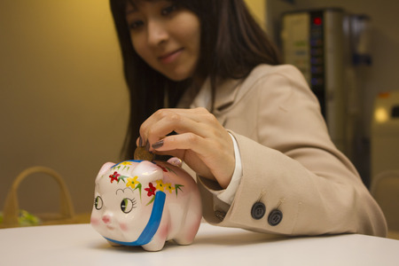 piggy bank: Young woman putting coin in piggy bank Stock Photo