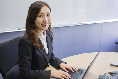 working woman: Young woman working with PC in office