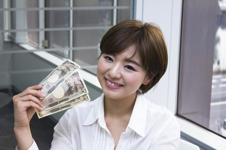Young woman holding Japanese Yen