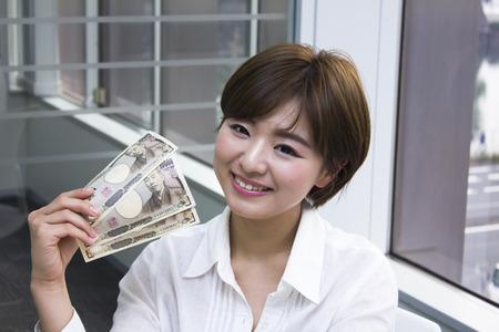 japanese yen: Young woman holding Japanese Yen Stock Photo
