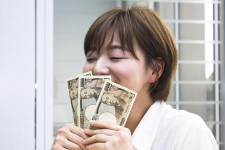 일본 엔을 들고 젊은 여자