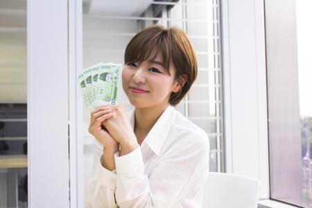 won: Young woman holding Korean Won