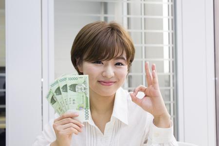 won: Young woman holding Korean Won with OK sign Stock Photo