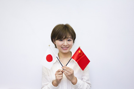 japanese flag: Young woman holding Japanese flag and Chinese flag