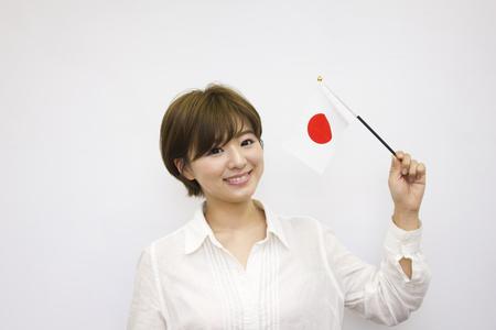 bandera japon: Young woman holding Japanese flag