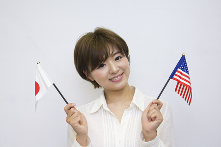 bandera japon: Young woman holding Japanese flag and American flag Foto de archivo