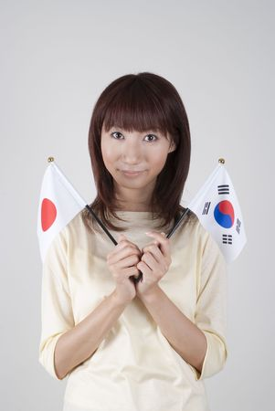 Young woman holding Japanese flag and Korean flag