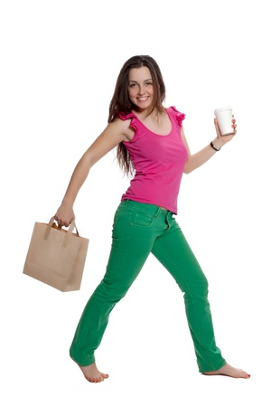 Beautiful girl with a bag and a coffee cup is walking Stock Photo