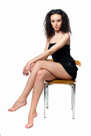 Beautiful girl with long legs sitting on a chair in the studio isolated on a white background photo