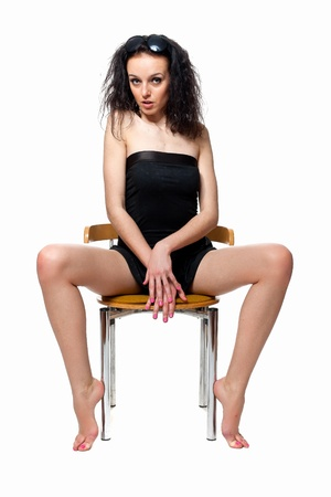 Beautiful girl with long legs sitting on a chair in the studio isolated on a white background Stock Photo - 10415719