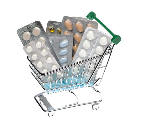 Shopping cart with different pills blister pack on an isolated background photo