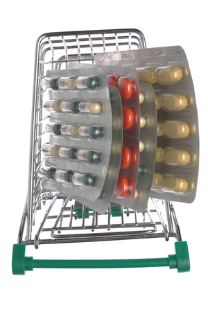 retail therapy: Shopping cart with different pills blister pack on an isolated background Stock Photo