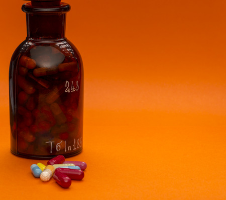 Glass bottle with pills and sopy space on orange background