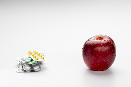 Red apple and colorful pills in blister on white background